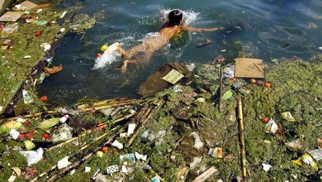 Enfant qui nage dans la rivière polluée de Chine